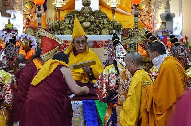 Mönche stehen um den Dalai Lama herum und händigen ihm Geschenke aus.
