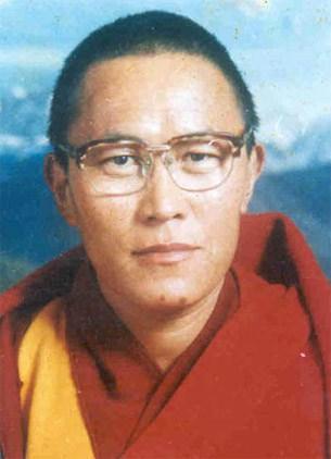 Tenzin Delek Rinpoche in Mönchsrobe vor blauem Hintergrund