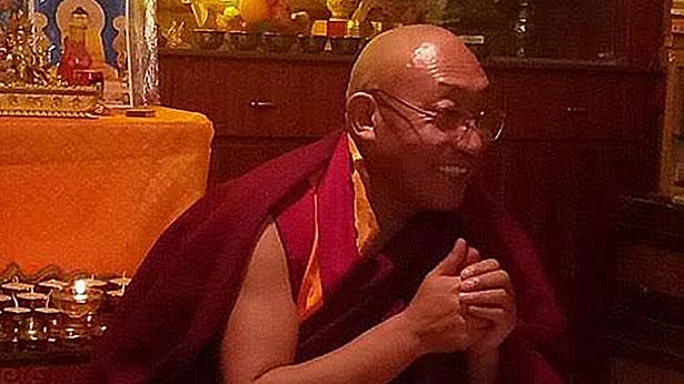 Mönch Atruk Lopo lacht und hat die Hände zusammen gelegt