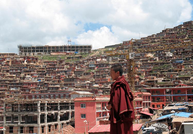 Mönch im Vordergrund, läuft vor Behausungen in Larung Gar im Hintergrund, schaut nachdenklich