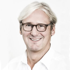 Portrait von Oberbürgermeister Jochen Partsch, er trägt eine Brille und ein weißes Hemd und lacht