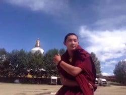 Mönch Lobsang Dhargya draußen vor Bäumen und Stupal