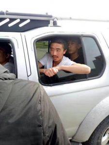 Ein Tibeter im T-shirt schaut aus dem Fenset eines Autos