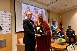 Ein Politiker überreicht einem Mömch stellvertretend für Tenzin Delek Rinpoche die Medaille