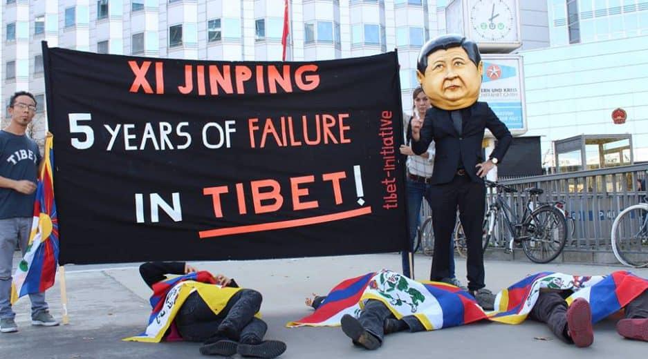Banner vor der chinesischen Botschaft, im Vordergrund ein Mensch als Xi Jinping verkleidet, davor Menschen mit tibetischer Flagge am Boden