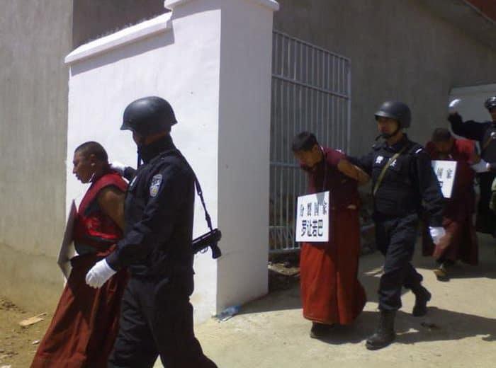 Tibetische Mönche werden von chineischem Militär abgeführt