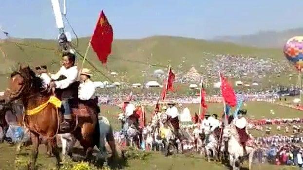 Tibeter auf Pferden tragen die chinesische Flagge