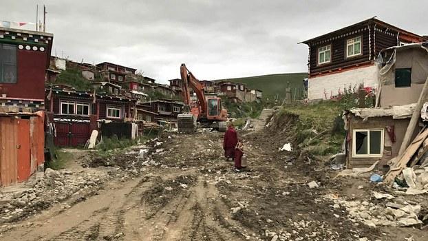 Ein Bagger auf einer Straße in Yachen Gar, zuvor standen hier noch Behausunger der Nonnen und Mönche