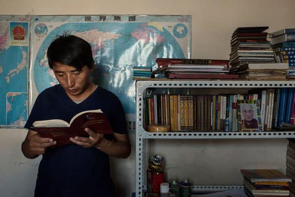 Tashi Wangchuk liest in einem buch, neben ihm steht ein Bücherregal