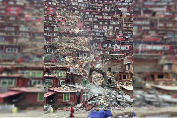 Ein Kran reist Behausung in Larung Gar ab, Mönch läuft im Vordergund die Straße lang
