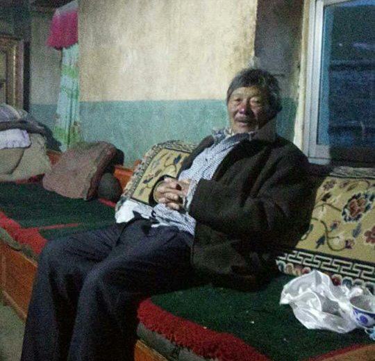 Alter Tibeter sitzt auf einer Bank und lächelt