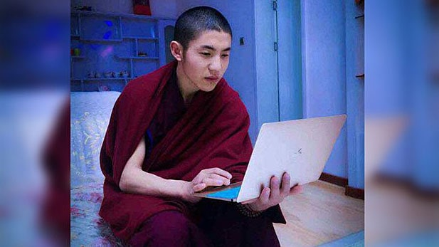 juger Mönch mit Lap Top in der Hand