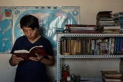 Tashi Wangchuk lehnt an einer Wand und liest in einem Buch, neben ihm ein Bücherregal