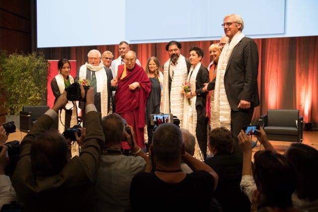 Gruppenfoto mit dem Dalai Lama, den Referenten, der Moderatorin, dem Cellisten Karim Wasfi, dem OB Jochen Partsch und unserem Vorsitzenden.