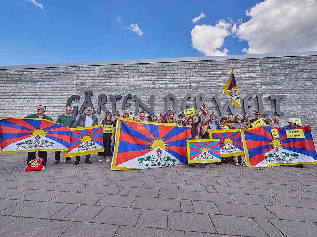 Mitglieder der Tibet Initiative Deutschland zeigen Tibet-Flaggen vor den Gärten der Welt in Berlin-Marzahn